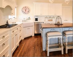 cote de texas breakfast room/kitchen renovated by Leslie Davies of LD Designs.  James Farmer painted the chairs, the bench and table a cream color, adding a slight aqua-blue line detailThe kitchen is all creamy white with aqua blue accents on the island and the stools and shade.