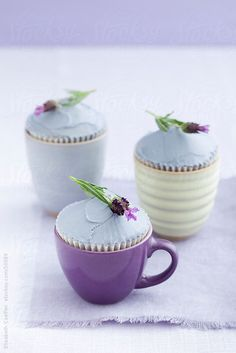 Three lavender cupcakes garnished with real lavender in cups  by Elisabeth Coelfen