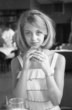 Goldie Hawn contemplating a hamburger, 1964.