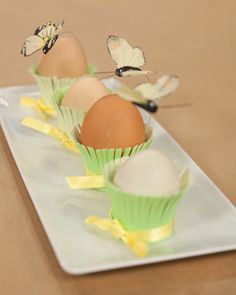 Make a fun and easy Easter table setting that guests will adore. Write names on a hard-boiled egg and then place inside an embellished paper hold.