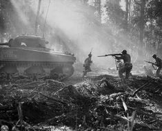American soldiers use a Sherman tank for cover as it and they advance on Japanese positions during the fight to take Bougainville, Solomon Islands, 1944.