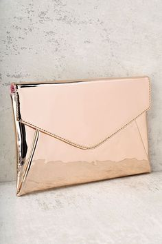 "You'll feel shiny and new with the New Image Rose Gold Clutch by your side! Metallic vegan leather folds into an envelope-style clutch. Lift flap from hidden magnetic closure to reveal a roomy interior and zippered pocket to hold all your goodies. Carry as a clutch or attach the 50"" silver chain strap."