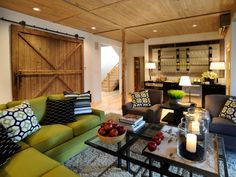 The cozy and conversational living room from HGTV Dream Home 2011 features a green sectional sofa, shaggy rug and kitchenette for quick access to snacks and drinks. A vintage barn door serves as both a conversation and an art piece.