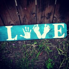 Home decor sign made from old fence wood panel- using my daughter's hand print and footprints to spell out LOVE
