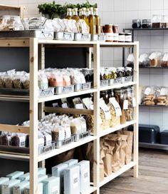 Estantes de madeira com tabuleiros em aço inoxidável com sacos de cuscuz e especiarias