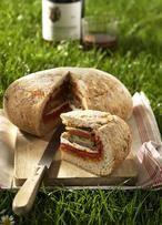 Ausgehöhltes Brot und gefüllt mit Tomaten-Pesto, Gurke, Käse, Basilikum, Paprika und Salami für ein super Picknick