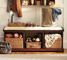mudroom/entryway bench, dark wood with light cushion; paneling; small cupboards; baskets
