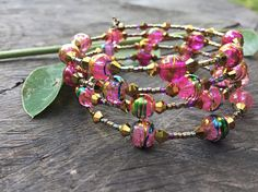 A gorgeous pink and gold bracelet made on memory wire. It has 5 layers of memory wire and features golden seed beads with pink hues and pink drizzle glass beads. It fits most hands and it does not lose its form (memory wire) easily.