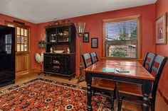 Dining room makeover: Country Dining Room with Glass panel door, double-hung window, Carpet, Paint, Standard height, Built-in bookshelf. Chinese Red SW 0057 from Sherwin Williams.