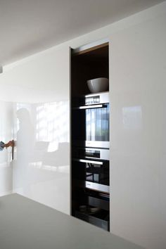 Clever hidden kitchen in glossy white by Minosa Design _
