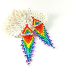 Beaded dangle earrings with fringe. Seven colors of the rainbow. Red - orange - yellow - green - blue - indigo - violet and silver. Pattern designed by me.  Length: 11.8 cm (4.7 inches) Width: 2.8 cm (1.1 inch)  I suggest you look at the similar product rainbow with black https://www.etsy.com/listing/213898165 black, blue, red https://www.etsy.com/listing/216184135 yellow, red, blue, black https://www.etsy.com/listing/270432502 golden, bronze, white https://www.etsy.com/listing/270281615…