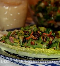 Old Fashioned Broccoli Salad - made with red onion, celery, carrots, raisins, nuts and bacon, and a mayonnaise, vinegar and sugar dressing. Served here on leaves of romaine lettuce.