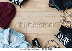 Flat lay fashion set : Jean jacket, sunglasses, hat, leather backpack, shoes and accessories. Negative space in the middle  - stock photo