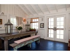 love the rustic wood table and benches set against the white painted beams and french doors.  Sigh....