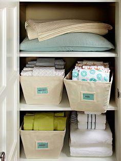 Organized linen closet--bins for sheets!  Genius!!