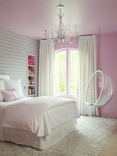 Pink and gray girl's bedroom features a pink ceiling over pink walls framing arched windows ...