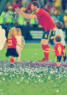 Xabi Alonso playing with a herd of Spanish National Team babies after the Euro win. Too cute.