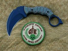 """Airborne Knives Yakuza Karambit - Overall Length: 7-1/8'' Blade Length:4"""" Blade Material: A2 Tool Steel Blade Finish: Flat Black Cerakote Thickness: 7/32"""" Blade Grind: Hollow ground double edge Handle Material: G10 Sheath: Custom fit kydex quick draw sheath Extra features: pain compliance ring spike. $374.99"""