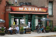 """Madiba: The name """"Madiba"""" pays homage to Nelson Mandela. Go here to try incredible south african food. Try the Corn Fed Half Cornish Hen Peri Peri, the bunny chow or the Durban samosas. In the evenings and on weekends, this place becomes a boisterous neighborhood joint."""