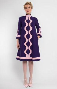 A-shape genuine wool dress trimmed with ribbon. Band collar. Bell-bottom sleeves with idle buttons. Hidden back zip closure. Side seam pockets.