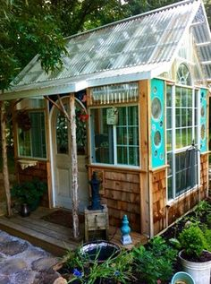 Garden Potting Shed built with salvaged parts :: Note the little round windows - they are vintage plates, set into wood panels...