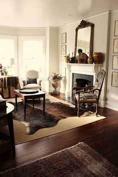 This room has it all--color, texture, light, beautifully pantina'd antiques, seagrass mat, cowhide rug, nature accessories, pottery.