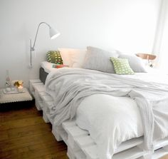 White pallet bed, gray and colored pillows, reading light, and a tool for a bedside table. ♥