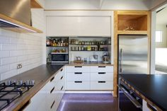 A large tambour door rolls up to reveal storage for small appliances, spices and oils.