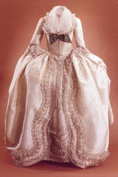 Robe à l'Anglaise, England, 1780-1789. Dark ivory silk taffeta; open front skirt is cartridge pleated at waistline and has small silk loops on under seams which allows side panels to be drawn up in Polonaise fashion. Matching petticoat and gown are elaborately trimmed with fancy cream silk gauze which is ruched and puffed and applied in undulating furbelows from waist to hem, and in deep flounces and undulations on petticoat front.