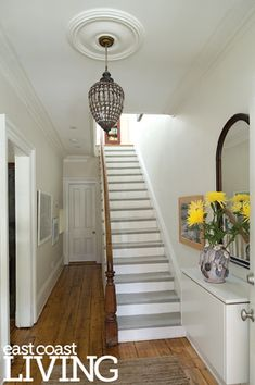 Narrow hallways and stairways are typical of row houses of this period. But with white walls and minimal décor, the space opens up beautifully. Narrow Entryway, Narrow Hallways, Front Stairs, Flur Design, Stair Decor, Hallway Designs, Hallway Ideas, Hallway Lighting, Minimal Decor