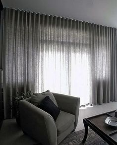 These sheer black curtains span a whole wall, adding another dimension of texture to the space. Style Ripplefold, for more information go to http://www.bqdesign.com.au/curtains