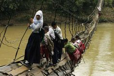 When bridges collapse from flooding or age, they must tightrope walk across them like these children are doing from Sanghiang Tanjung village.