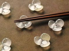 瑞々しく透明感のある、花びらの形の箸置きになります。 一片には淡いベージュ色のガラス生地を組み合わせています。 熱によって少しずつ溶け合うガラスの滑らかなシルエットを、そのまま表情に留めました。 表面にはアクセントに細い線刻を施しています。 作品全体に点在する白い粒々は細かな気泡になりますが、これはガラスの粒が熔け合う時に空気を閉じ込める為で、この表情は鋳造ガラスの特長の一つになります。細かな気泡を含むガラスには、柔らかさやどこか懐かしさが感じられます。 ※素材 : ガラス ※価格 : 1点のお値段として表示しております。 ※色・形 : こちらの作品は画像2枚目と3枚目左上のお色になり、一片には淡いベージュ色を組み合わせています。画像はサンプル作品ですので色の濃淡など多少の誤差はご了承ください。 また形も熔け具合によって一点一点に多少の変化がございます。 ※サイズ : 縦35−40mm × 横35−40mm × 高さ 10mm(約) ※重さ : 約15g ※ギフト包装(箱無し)も無料で承ります。ご注文の際にメッセージにてお知らせください。 ... Chopstick Holder, Chopstick Rest, Home Decor Accessories, Handmade Accessories, Japan Crafts, Ceramic Flowers, Chopsticks, Ceramic Plates, Glass Design