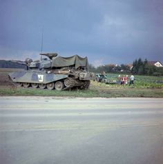 Work goes on as usual for German farm family, although a 52 ton Canadian Centurion tank has just clanked into the field behind them. It was during Exercise Reforger 74 in Germany during October,1974.