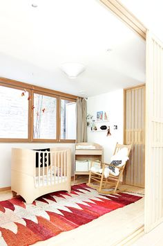 A copper mobile by JF Jones hangs over a Leander crib and a vintage Moroccan rag rug in the nursery. The rocking chair is by Hans Wegner for Fredericia. Photo by: Derek ShaptonCourtesy of: Derek Shapton Mjölk Boutique Owners Renovate Their Toronto Abode Nursery Room, Girl Nursery, Kids Bedroom, Nursery Office, Boho Nursery, Nursery Decor, Style Californien, Design Japonais, Wood Crib