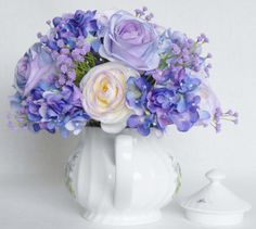 This listing is for a Lovely Teapot Silk Flower Arrangement of Beautiful Lavender Roses, Multi-Color Pastel Ranunculus and Tiny Hydrangea in shades of Purple, Lavender and Blue. I arranged them in a beautiful 5 inch high white teapot with a spiral design decorated with lavender