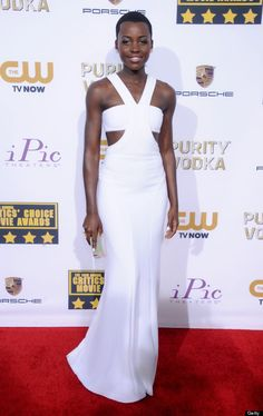 Lupita Nyongo Critics Choice Awards wearing a white silk crepe cutout gown by Calvin Klein Collection, finished off with a Calvin Klein Collection box clutch, Paul Andrew custom shoes and Kimberly McDonald Jewelry.