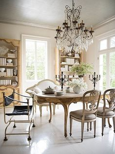 French dining chairs, a gilded carved leg oval dining table, ivory love seat and oversized crystal chandelier make for a seriously glamorous dining room!