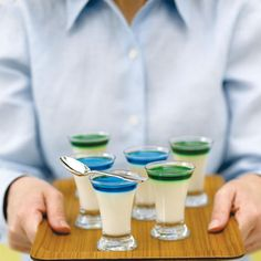 Panna cotta shots served in shot glasses and topped with neon-colored liqueurs and syrups.