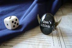 """Très jolie bague vintage sur le thème de la série britannique Doctor Who et ses fameux Anges Pleureurs, avec son texte emblématique """"Don't blink !"""" écrit façon vieille machine à écrire en blanc sur noir sous cabochon de verre, et ses ailes collées au support de la bague de chaque côté.    Retrouvez-la ici : http://www.alittlemarket.com/bague/_reserve_silverleaf_bague_a_cabochon_doctor_who_don_t_blink_-3120323.html"""