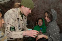 This Canadian soldier is helping and caring an Afghanistan girl that is injured. by Omen and Daniel Lee CHC Pictures Of Soldiers, Canadian Soldiers, Imagine John Lennon, Amazing Grace, Afghanistan, Military Jacket, Faces, War, Fashion