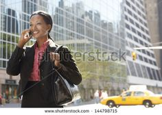 Smiling African American businesswoman using mobile phone on street against building - stock photo