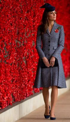 """The Duchess of Cambridge surprised us by finishing out the Australian tour in a Michael Kors Indigo Swing Coat (SS14). She accessorized with her Alexander McQueen navy suede pumps, Stuart Weitzman """"Muse"""" clutch, diamond and sapphire drop earrings, Asprey London woodland charms necklace, Cartier watch, Russian Poppy Brooch from the MET Museum and Jonathan Howard """"Boutton"""" fascinator in Duchess Navy."""