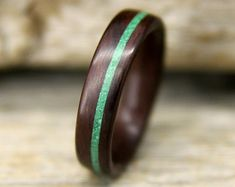 This listing is for a wearable, durable wooden ring, made to your size from Ziricote Rosewood, with an offset crushed turquoise inlay. The first rings shown are approx. 8mm wide. The inlay is approx. 1mm wide. The variances in color occur naturally. If you would like a certain shade, please leave a comment in the message section when checking out. Each ring is carefully handcrafted using the bentwood method. No lathe is involved. The woods grain is oriented around the circumference of the…