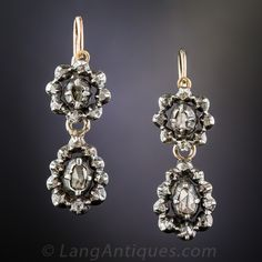 Late Georgian~Early Victorian Rose-Cut Diamond Earrings. A dark and dramatic pair of antique diamond earrings hailing from the early-to-mid-nineteenth century. These possibly Georgian, but at the very least early-Victorian, diamond drops glisten with two pairs of diamond centered halos of rose-cut diamonds set in deeply patinated silver over 9K gold. Enchanting original antique jewels measuring just shy of one inch long.