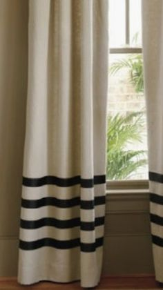 add grosgrain ribbon to make stripes on DIY drop cloth curtains.