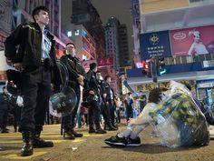 Umbrella Revolution Hong Kong, 01:52, 23OCT2014, a student protester taking a nap at the front line to protect the protest site in Mong Kok.  十月二十三日,昨日朗豪坊旁邊亞皆老街的路障被人清除,之後一隊軍裝警察駐守在此,防止有人再築路障。晚上大雨滂沱,仍有小數市民席地坐在警員面前,照片中的女子倦極而睡。記者 : Daniel Cheung  https://www.facebook.com/socrec/photos/a.166189016741371.44945.160696287290644/1000989156594682/?type=1&theater