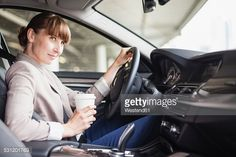 Stock Photo : Germany, Hesse, Frankfurt, portrait of smiling businesswoman driving car with coffee to go in one hand