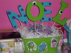 Cake table decoration with my babys name! Made out of wood letters & a basket from the dollar store, filling from the easter baskets, Styrofoam, wood sticks. & some monsters inc printables that i color.