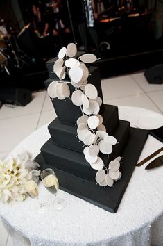 black four tiered square wedding cake on a black cake stand with white design draping down cake as topper - cake is on round table with white table cloth with bride and groom's champagne flutes and an ivory floral arrrangement -  photo by Houston based wedding photographer Adam Nyholt